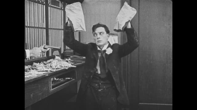 1921 despondent sticky bank teller (buster keaton) gets hands stuck in pockets just as bank robbery begins - hosentasche stock-videos und b-roll-filmmaterial