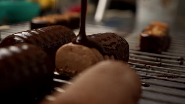 dessert chef covering a cake biscuit on a popsickle with a melted black chocolate on a metal net tray - b roll stock videos & royalty-free footage
