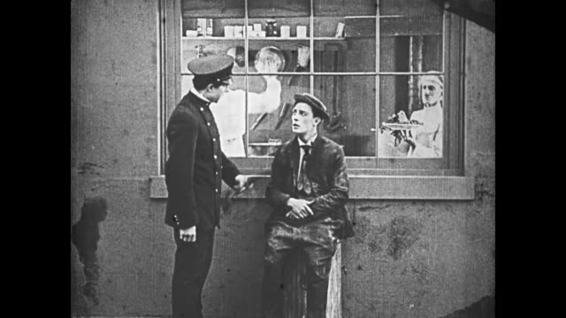 vídeos de stock e filmes b-roll de 1921 a destitute man (buster keaton) plays with a policeman's night stick while sitting in front of a restaurant window - maça