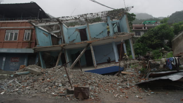 barabise, nepal - july 31, 2015: ws destroyed blue house at an angle, three people in house - earthquake stock videos & royalty-free footage