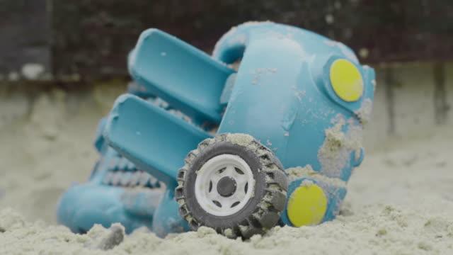 stockvideo's en b-roll-footage met vernietigd blauwe speelgoedauto op zand, speeltuin - echtscheiding