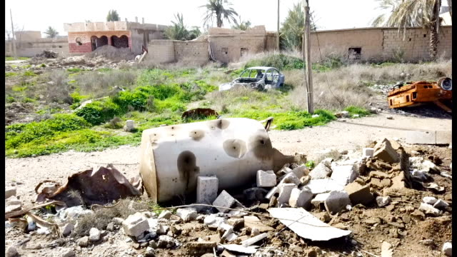 destroyed buildings and cars can be seen, civilians have begun returning to some small towns close to bagouz that were recently liberated by the... - isil konflikt stock-videos und b-roll-filmmaterial