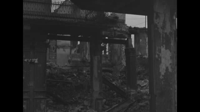 vs destroyed buildings lay in rubble and ruin / american soldier with rifle follows captured german army officer / vs more rubble debris destroyed... - rifle stock videos & royalty-free footage