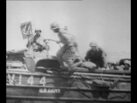 destroyed buildings on shore of leyte island in the philippines during us invasion / landing crafts arrive at shore / soldiers disembark / montage... - 多国籍軍点の映像素材/bロール