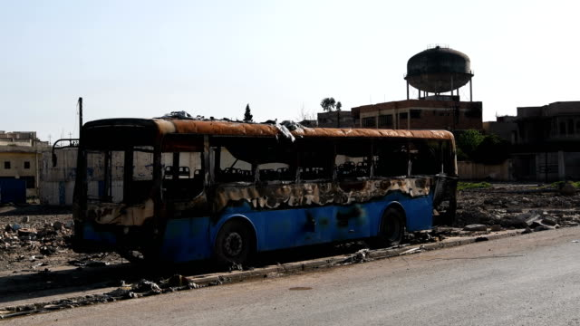 A destroyed burnt out bus in West Mosul Iraqi forces backed by US and British air support have entered their sixth month of fighting as they continue...