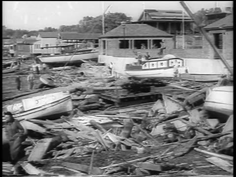 B/W 1938 destroyed fishing boats in marina after hurricane / Northeast US / newsreel