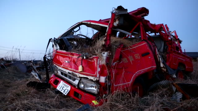 A Destroyed Red Truck sits in a Field