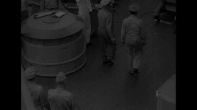 US destroyer alongside USS Missouri decks of both ships crowded with US military personnel / Gen Douglas MacArthur walks across gangway from...