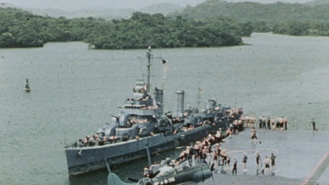 destroyer passing aircraft carrier with corsairs parked on the flightdeck on entrance to the canal / panama - panama canal stock videos & royalty-free footage