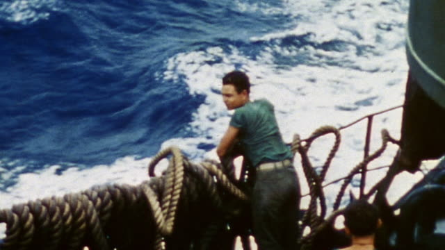 vídeos de stock e filmes b-roll de destroyer underway with sailor standing on deck, arms resting on ship's railing, watching rough waters and crashing waves on journey from ulithi to... - pacific war