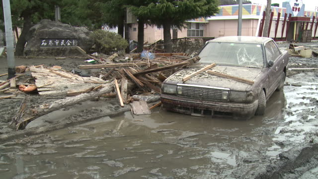 Destruction caused by tsunami after magnitude 9 Tohoku earthquake, north east Japan, March 2011. Car lies wrecked and caked in mud after tsunami in Ishinomaki City,  Miyagi Prefecture