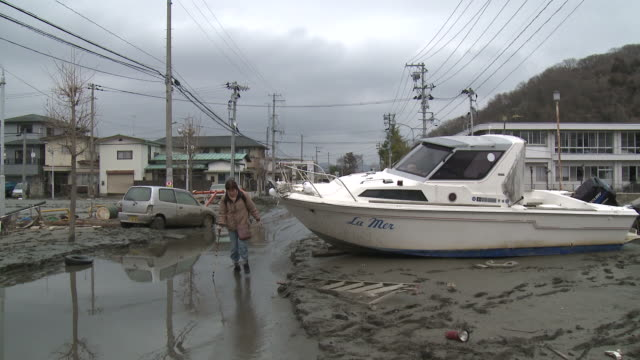 Destruction caused by tsunami after magnitude 9 Tohoku earthquake, north east Japan, March 2011. Woman walks past boat washed onto street by tsunami in Ishinomaki City,  Miyagi Prefecture