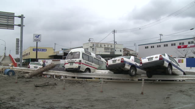 Destruction caused by tsunami after magnitude 9 Tohoku earthquake, north east Japan, March 2011. Cars lie piled in thick mud after tsunami in Ishinomaki City,  Miyagi Prefecture