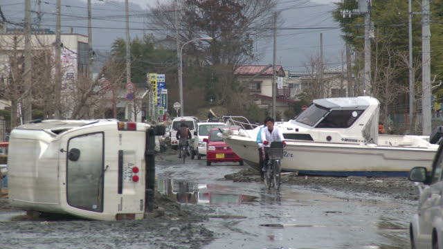 destruction caused by tsunami after magnitude 9 tohoku earthquake, north east japan, march 2011. people moves past wrecked car and boat after tsunami in ishinomaki city,  miyagi prefecture - tsunami stock videos & royalty-free footage
