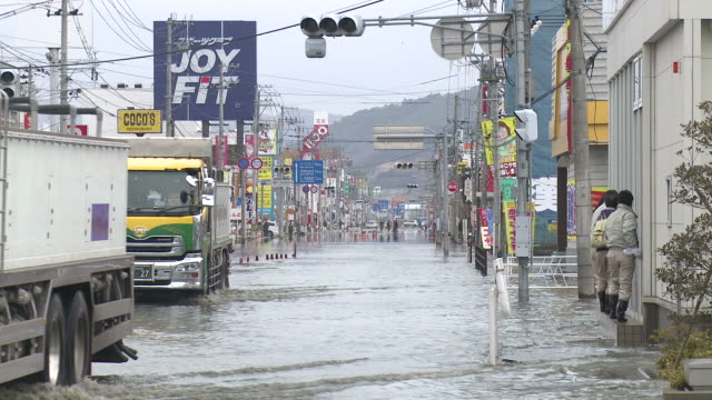 Destruction caused by tsunami after magnitude 9 Tohoku earthquake, north east Japan, March 2011. Trucks drive through tidal flooding in Ishinomaki, Miyagi Prefecture after tsunami