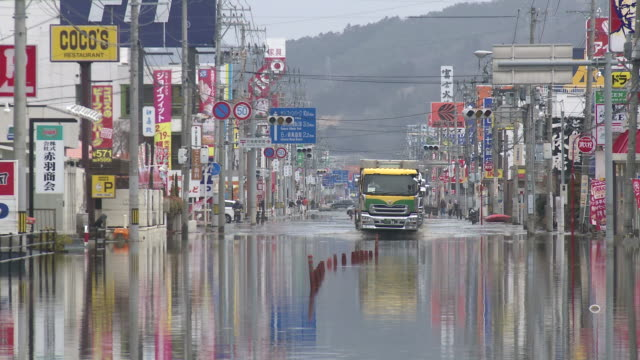 destruction caused by tsunami after magnitude 9 tohoku earthquake, north east japan, march 2011. trucks drive through tidal flooding in ishinomaki, miyagi prefecture after tsunami - tsunami stock videos & royalty-free footage