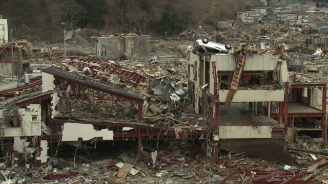 Destruction in Onagawa city, near Sendai Japan on 3rd April 2011; after tsunami following Tohuku earthquake of March 2011.  Car on roof of ruined building