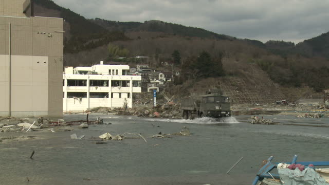 destruction in onagawa city, near sendai japan on 3rd april 2011; after tsunami following tohuku earthquake of march 2011.  military vehicle drives through tidal flooding in onagawa due to coastal area sinking after earthquake - tsunami stock videos and b-roll footage