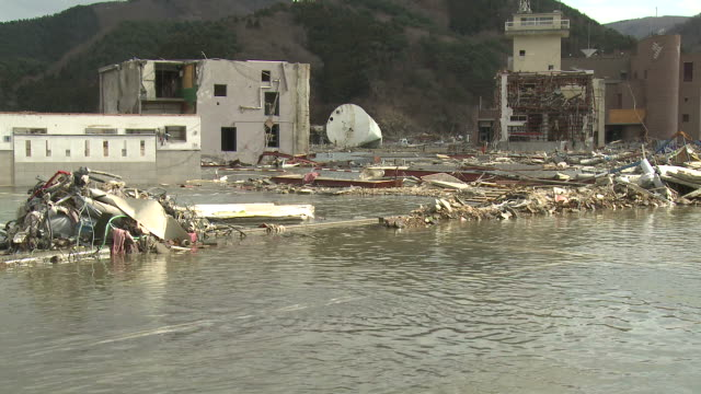 destruction in onagawa city, near sendai japan on 3rd april 2011; after tsunami following tohuku earthquake of march 2011.  tidal flooding in onagwa port due to coastal area sinking after earthquake - tsunami stock videos & royalty-free footage
