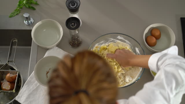 4K detail from above kneading dough in bowl