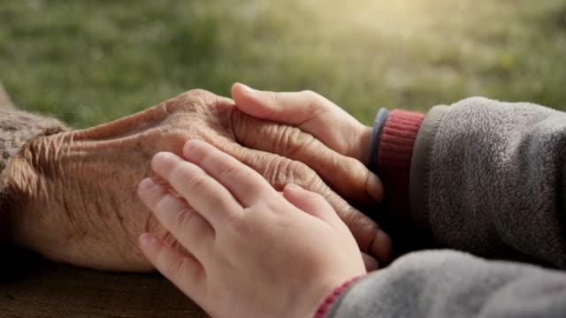 EINE HELFENDE HAND. Detail eines Kindes Hand hält die ältere Frau-Hände
