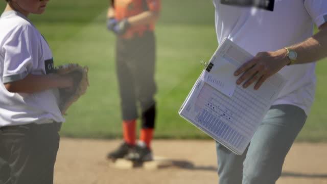 vídeos de stock, filmes e b-roll de detail of a coach and a player in a little league baseball game. - treinador