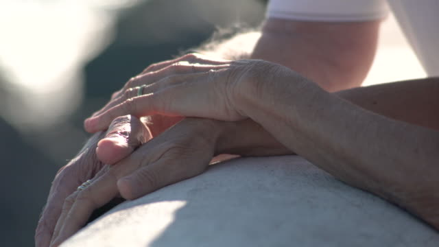 vídeos de stock e filmes b-roll de detail of a couple of seniors hands with a soft care touch on terrace by the sea - acariciar