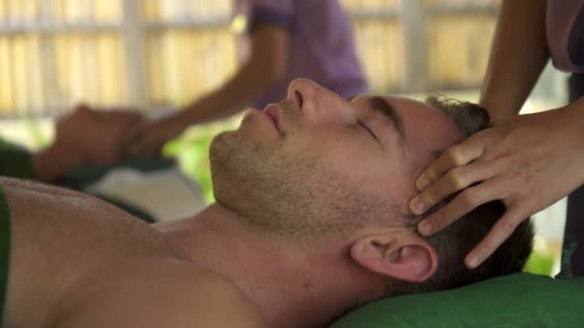 detail of a man getting a massage at a resort spa. - head massage stock videos & royalty-free footage
