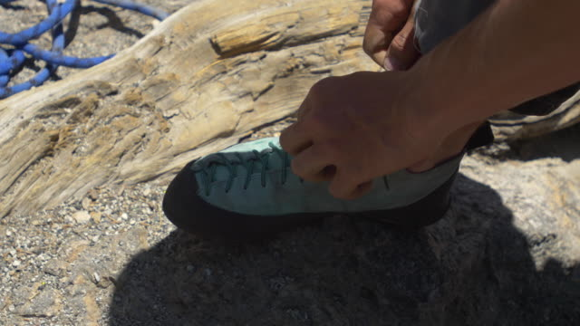 detail of a man putting on his rock climbing shoes. - human limb stock videos & royalty-free footage