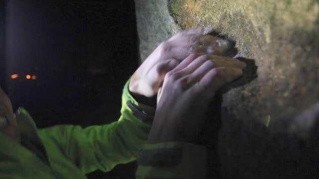 vidéos et rushes de detail of a manõs hands as he climbs boulders at night. - lampe frontale
