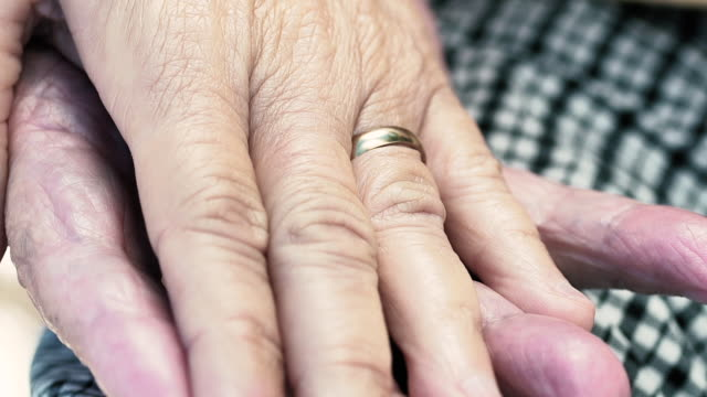 cu detail of a senior couple hand's with wedding ring. - tilt up stock videos & royalty-free footage