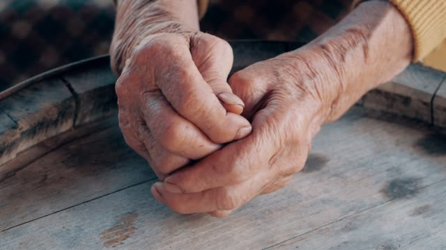 helping hand. detail of a senior woman hands - hands clasped stock videos and b-roll footage