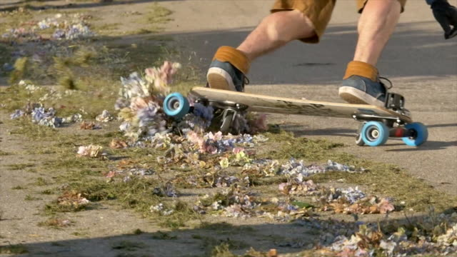 vídeos y material grabado en eventos de stock de detail of a skateboard going over some flowers while riding downhill. - slow motion - surf en longobard