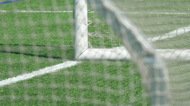 detail of a soccer football goal net and green turf field. - slow motion - tor konstruktion stock-videos und b-roll-filmmaterial