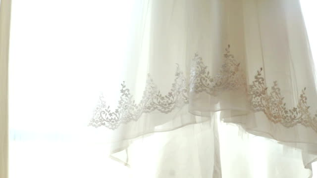 detail of a white wedding dress hanging in the room. - lace textile stock videos & royalty-free footage