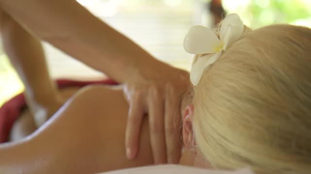 stockvideo's en b-roll-footage met detail of a woman getting a massage at a resort spa. - menselijke rug