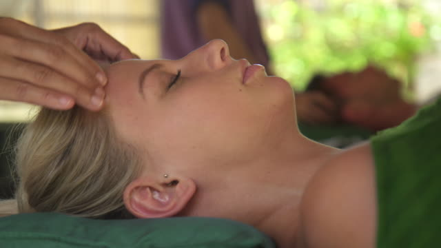 detail of a woman getting a massage at a resort spa. - head massage stock videos and b-roll footage