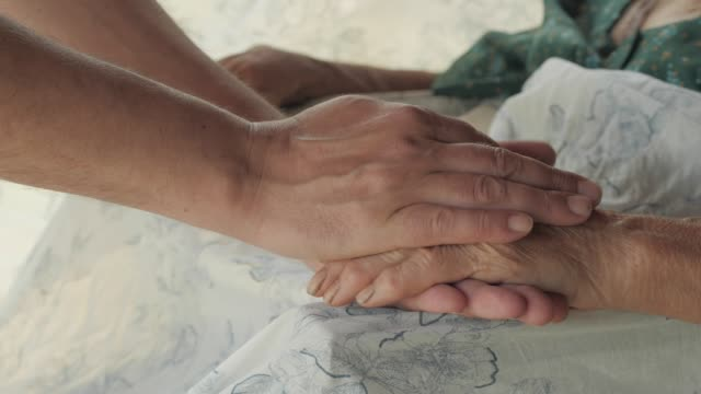 救いの手。年配の女性の手を繋いでいる若い男の手の詳細 - 依存点の映像素材/bロール