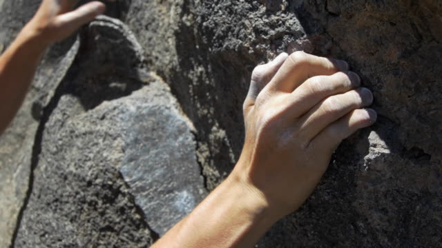 Detail of a young man rock climbing and grabbing a hold.