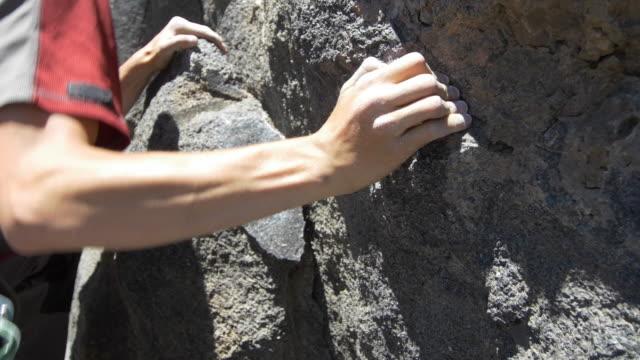 vídeos y material grabado en eventos de stock de detail of a young man rock climbing and grabbing a hold. - magnesio