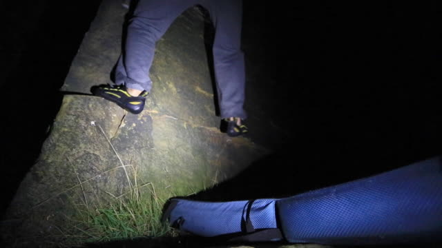 vidéos et rushes de detail of a young manõs shoes as he climbs boulders at night. - lampe frontale