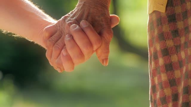 vídeos y material grabado en eventos de stock de una mano de ayuda. detalle de una mujer joven las manos sosteniendo las manos de mujer senior - 80 89 años