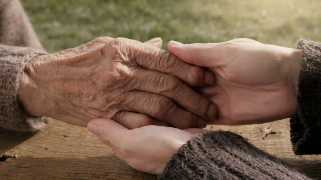 A HELPING HAND. Detail of a Young Woman Hands Holding the Senior Woman Hands