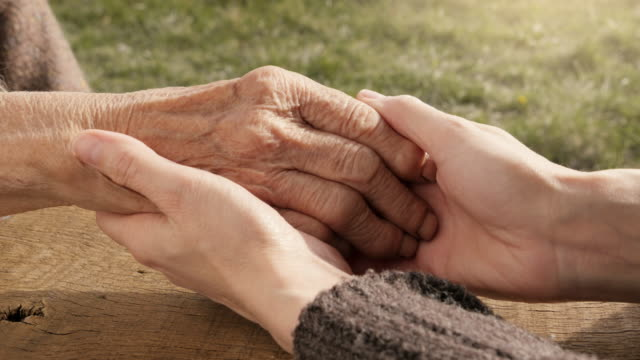 a helping hand. detail of a young woman hands holding the senior woman hands - hands clasped stock videos and b-roll footage