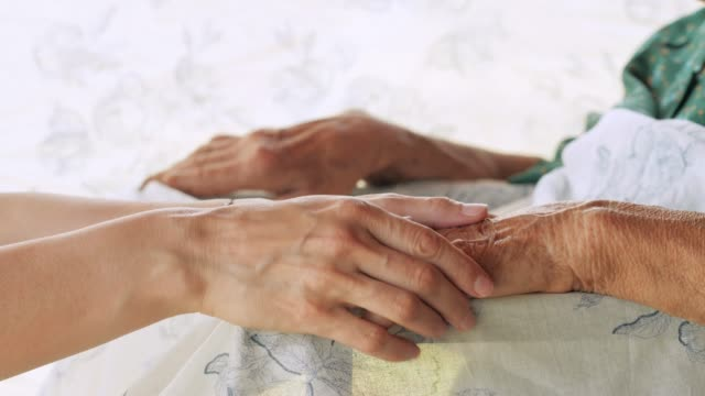 a helping hand. detail of a young woman hands holding the senior woman hands - active seniors stock videos & royalty-free footage