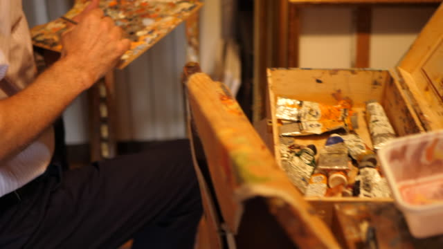 detail of an artist hand and paint palette as he paints an oil painting on canvas inside his art studio. - slow motion - oil paint stock videos and b-roll footage