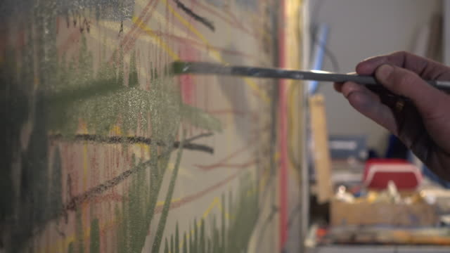 Detail of artist painting canvas, in studio