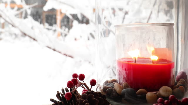 detail of candle and christmas wreath, snowy forest behind - christmas decore candle stock videos & royalty-free footage