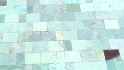detail of clear swimming pool with water and natural stone tile floor