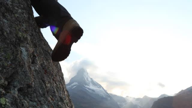 detail of climber's boots scaling steep rock, matterhorn distant - rock climbing stock videos & royalty-free footage